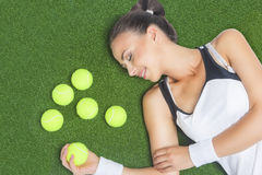 Female Tennis Player Lying on Artificial Grass Surface With Tenn Royalty Free Stock Photos