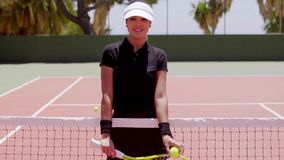 Female tennis player at net with ball and racket stock footage