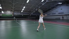 Female tennis player playing on indoor court against male player. She winning and jumping for joy. Sport leisure stock video
