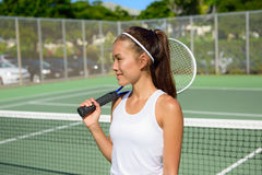 Female tennis player portrait with tennis racket. Outdoors in tennis court in summer. Fit female athlete playing tennis living healthy active sport and fitness Royalty Free Stock Images