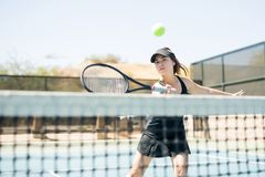 Female tennis player practising on court. Good looking female tennis player hitting the ball over the net on court Stock Photos