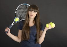 Female tennis player with racket and ball on black background Royalty Free Stock Photography