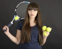 Female tennis player with racket and ball on black background Royalty Free Stock Photos