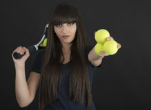 Female tennis player with racket and ball on black background Royalty Free Stock Images