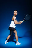 Female tennis player with racket ready to hit a ball. Stock Photography