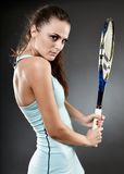 Female tennis player with racket. A studio shot of a young female tennis player executing a backhand strike Royalty Free Stock Images