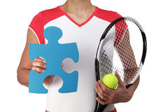 Female tennis player showing a piece of puzzle Royalty Free Stock Image