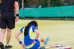 Female tennis player is sitting on the court Royalty Free Stock Images