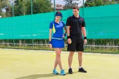 Female tennis-player throwing tennis ball near her partner Stock Photo