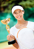 Female tennis player won the competition. Tennis player won the cup at the sport competition. Victory Royalty Free Stock Photography