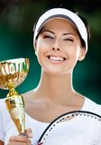 Female tennis player won the match. Tennis player won the cup at the sport contest. Victory Stock Photography