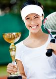 Female tennis player won the tournament. Female tennis player won the cup at the sport competition. Prize Stock Image