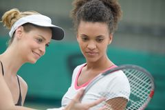 Female tennis players checking racquet Royalty Free Stock Photos