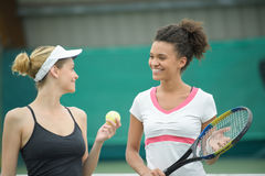 Female tennis players talking at clay court. Female tennis players talking at a clay court Stock Photography