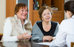 Female therapeutist consulting senior patients in clinic Stock Photography
