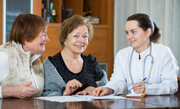 Female therapeutist consulting senior patients in clinic Stock Photo