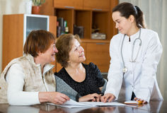 Female therapeutist consulting senior patients in clinic Royalty Free Stock Photos