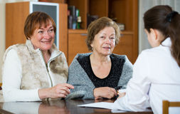 Female therapeutist consulting senior patients in clinic Royalty Free Stock Images