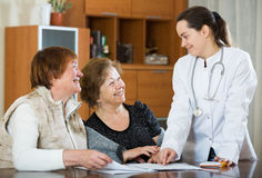 Female therapeutist consulting senior patients in clinic Royalty Free Stock Photography