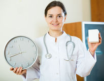 Female therapeutist in white overallwith clock and remedy Stock Photos