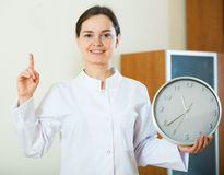 Female therapeutist in white overallwith clock and remedy Stock Photography