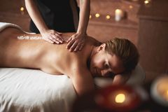 Female therapist apply mineral salt on lady back stock image