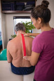 Female therapist applying elastic therapeutic tape on back of shirtless senior male patient Stock Photos