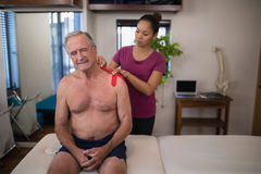 Female therapist applying elastic therapeutic tape on shoulder of frowning shirtless senior male pat Stock Photos