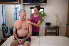 Female therapist applying elastic therapeutic tape on shoulder of shirtless senior male patient Stock Images