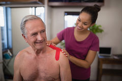 Female therapist applying elastic therapeutic tape on shoulder of smiling shirtless senior male pati Stock Photos