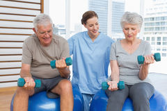 Female therapist assisting senior couple with dumbbells Royalty Free Stock Image