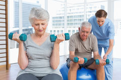 Female therapist assisting senior couple with dumbbells Royalty Free Stock Photos