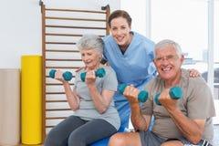 Female therapist assisting senior couple with dumbbells Stock Image