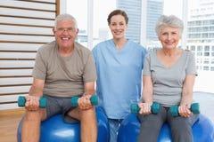 Female therapist assisting senior couple with dumbbells Stock Photo
