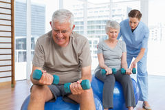 Female therapist assisting senior couple with dumbbells Stock Photography