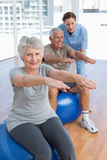Female therapist assisting senior couple with exercises Stock Photos