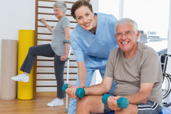 Female therapist assisting senior man with dumbbells Stock Image