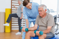 Female therapist assisting senior man with dumbbells Stock Photography