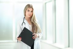 Female therapist with a clipboard, standing near the hospital window royalty free stock photos