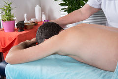 Female therapist doing back massage on man body. Female therapist doing back massage on men body in the spa salon Stock Image