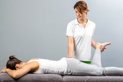 Female therapist doing osteopathic leg manipulation on patient. Close up of female physiotherapist doing manipulative leg therapy on patient.Therapist relieving Royalty Free Stock Image