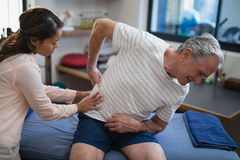 Female therapist examining back of senior male patient sitting on bed Stock Photography