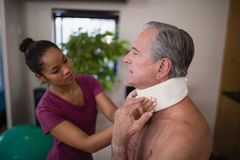 Female therapist examining neck collar on senior male patient. At hospital ward royalty free stock images
