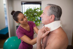 Female therapist examining neck collar of senior male patient. At hospital ward stock photo
