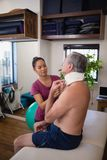 Female therapist examining neck collar of senior male patient sitting on bed. At hospital ward stock photography