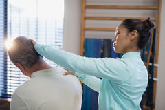 Female therapist examining neck of senior male patient. At hospital ward royalty free stock photos