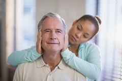 Female therapist holding head of senior male patient Stock Photography