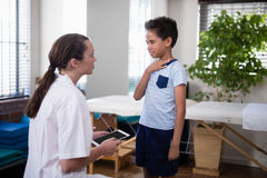Female therapist looking at boy touching neck. At hospital ward Royalty Free Stock Photography