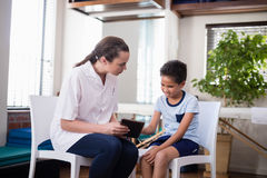 Female therapist looking at boy while using digital tablet. At hospital ward Stock Images
