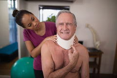 Female therapist looking at senior male patient grimacing with neck collar. In hospital ward stock photo